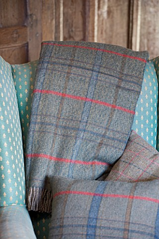 FULBROOK_HOUSE_SITTING_ROOM__ARMCHAIR_WITH_WOOL_PLAID_THROWS_AND_CUSHION_FROM_COTSWOLD_WOOLLEN_WEAVE