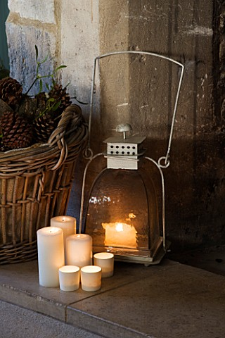 FULBROOK_HOUSE_SITTING_ROOM__COTSWOLD_STONE_FIRE_HEARTH_WITH_LOG_BASKET__METAL_LANTERN_AND_CANDLES