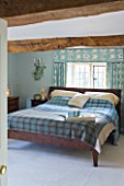 FULBROOK HOUSE: MASTER BEDROOM; BEAMED CEILING  AQUA PAINTWORK AND PRINTED LINEN CURTAINS COORDINATE WITH AQUA PLAID WOOL THROW FROM COTSWOLD WOOLLEN WEAVERS
