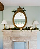 FULBROOK HOUSE: MASTER BEDROOM; COTSWOLD STONE MANTELPIECE WITH ANTIQUE GILT MIRROR TRIMMED WITH PINE FOR CHRISTMAS