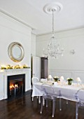 WHITE HOUSE: WHITE DINING ROOM WITH CENTRAL GLASS CHANDELIER AND SILVER ROUND MIRROR ABOVE MANTEL PIECE. LONG DINING TABLE DRESSED IN WHITE LINEN WITH TRANSPARENT GHOST CHAIRS