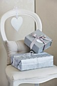 WHITE HOUSE: FAMILY ROOM - PAINTED WHITE WOODEN DINING CHAIR WITH SILVER GIFT WRAPPED PRESENTS