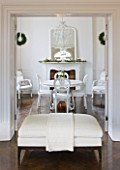 WHITE HOUSE: VIEW INTO BREAKFAST ROOM WITH IVORY UPHOLSTERED POUF  WHITE PAINTED TABLE AND CHAIRS  GLASS CHANDELIER AND WHITE FRAMED MANTLE MIRROR
