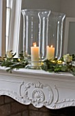 WHITE HOUSE: BREAKFAST ROOM: WHITE DECORATIVE MANTELPIECE WITH MIRROR DRESSED WITH GLASS HURRICANE LANTERN  PINE  EUCALYPTUS AND WHITE ROSES FOR CHRISTMAS.