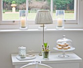WHITE HOUSE: BREAKFAST ROOM: WHITE SIDE TABLE SET WITH GLASS HYACINTH POT AND GLASS DOMED CAKE STAND WITH MINCE PIES