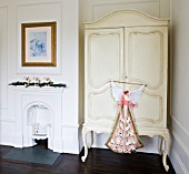WHITE HOUSE: GIRLS BEDROOM - DARK WOODEN FLOORS  VICTORIAN FIREPLACE AND CREAM PAINTED ARMOIRE WITH CHRISTMAS ADVENT ANGEL.