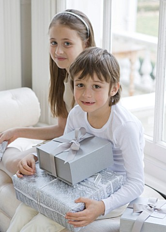 WHITE_HOUSE_GIRL_AND_BOY_IN_DINING_ROOM_SITTING_ON_WINDOW_SEAT_WITH_CHRISTMAS_PRESENTS