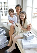 WHITE HOUSE: MOTHER WITH HER TWO CHILDREN AND PET DOG IN DINING ROOM SITTING ON WINDOW SEAT WITH CHRISTMAS PRESENTS
