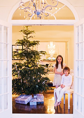WHITE_HOUSE_VIEW_THROUGH_DOUBLE_FRENCH_DOORS_INTO_LIVING_ROOM__BOY_AND_GIRL_ON_SEAT_WITH_CHRISTMAS_T