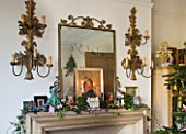 SARAH BAKERS HOUSE  THE OLD VICARAGE  SOMERSET: SITTING ROOM MANTLEPIECE WITH METAL WALL CANDLE SCONCES AND MIRROR  DECORATED WITH IVY FOR CHRISTMAS.