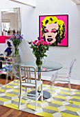 TARA NASH-KING HOUSE  LONDON: THE DINING AREA IN THE HOME OF CLOTHES DEALER TARA NASH-KING. TABLE  CHAIRS  MARILYN MONROE PRINT ON WALL