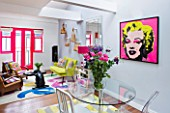 TARA NASH-KING HOUSE  LONDON: THE LIVING ROOM OF CLOTHES DEALER TARA NASH-KING. DINING TABLE AND CHAIRS  MARILYN MONROE PRINT ON WALL
