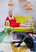 TARA NASH-KING HOUSE  LONDON: TARA NASH-KING LYING ON A DESIGNERS GUILD LINEN SOFA WITH GRAHAM & GREEN EMBROIDERED CUSHIONS IN THE LIVING ROOM OF HER NOTTING HILL MEWS HOME