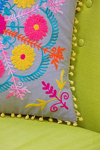 TARA_NASHKING_HOUSE__LONDON_LIVING_ROOM__CLOSEUP_OF_EMBROIDERED_FOLKLORE_CUSHION_FROM_GRAHAM__GREEN