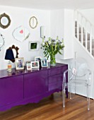 TARA NASH-KING HOUSE  LONDON: LIVING ROOM - VINTAGE MIRRORS DISPLAYED ABOVE BLACK CABINET PAINTED WITH PURPLE GLOSS PAINT  PHILIPPE STARCK GHOST CHAIR