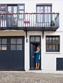 TARA NASH-KING HOUSE  LONDON: TARA NASH-KING OUTSIDE HER MEWS HOME  WITH FAKE TRAILING ROSES WOUND AROUND THE BALCONY