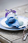 FISHING COTTAGE  KNEBWORTH PARK: STYLING BY JACKY HOBBS: TABLE ON JETTY BESIDE LAKE  WITH TABLE SETTING WITH BLUEBELLS IN GLASS CONTAINER ON PLATE WITH BLUE NAPKIN - SPRING