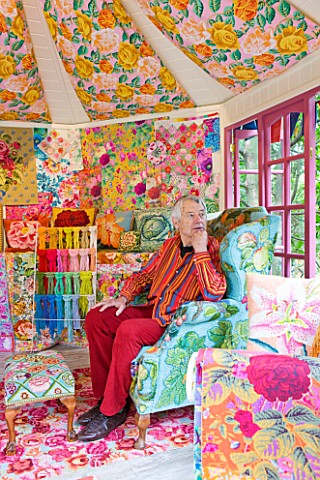 CHELSEA_2012__KAFFE_FASSETT_SITS_INSIDE__A_SHED_DECORATED_BY_HIM_WITH_NEEDLEPOINT_DESIGNS