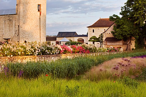 CHATEAU_DU_RIVAU__LOIRE_VALLEY__FRANCE_THE_CHATEAU_IN_THE_EVENING_WITH_SESLERIA_AUTUMNALIS__ALLIUM_G