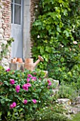 LES JARDINS DE ROQUELIN  LOIRE VALLEY  FRANCE: A VINTAGE WATERING CAN ON THE15TH CENTURY FARMHOUSE STEPS WITH ROSE ROSERAIE DE LHAY