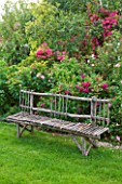 LES JARDINS DE ROQUELIN  LOIRE VALLEY  FRANCE: LAWN AND A DECORATIVE WOODEN CHESTNUT SEAT/ BENCH BY STEPHANE CASSINE BESIDE ROSE HENRI MARTIN AND ROSE MARIA LISA