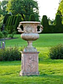 NYMANS  SUSSEX. THE NATIONAL TRUST: URN ON MAIN LAWN WITH TOPIARY YEW HEDGING BEHIND  EVENING LIGHT  JUNE