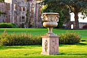 NYMANS  SUSSEX. THE NATIONAL TRUST: URN ON MAIN LAWN WITH THE HOUSE BEHIND  EVENING LIGHT  JUNE