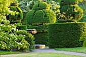 NYMANS  SUSSEX. THE NATIONAL TRUST : VIEW TO TOPIARY  CLIPPED YEW AND ITALIAN MARBLE FOUNTAIN. WALL GARDEN  JUNE  EVENING LIGHT