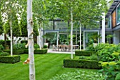 THE GLASS HOUSE  PETERSHAM. ARCHITECTS TERRY FARRELL PARTNERS. GARDEN DESIGN BY SALLIS CHANDLER: VIEW ACROSS LAWN TO LIMESTONE PATIO WITH TABLE AND CHAIRS  BETULA JACQUEMONTII