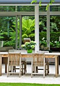 THE GLASS HOUSE  PETERSHAM. ARCHITECTS TERRY FARRELL PARTNERS. GARDEN DESIGN BY SALLIS CHANDLER: LIMESTONE PATIO  TABLE AND CHAIRS  VIEW THROUGH GLASS PAVILION TO TREE FERN GARDEN
