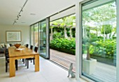 THE GLASS HOUSE  PETERSHAM. ARCHITECTS TERRY FARRELL PARTNERS. GARDEN DESIGN BY SALLIS CHANDLER: VIEW OUT OF HOUSE TO GARDEN WITH TABLE AND DECKING