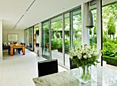 THE GLASS HOUSE  PETERSHAM. ARCHITECTS TERRY FARRELL PARTNERS. GARDEN DESIGN BY SALLIS CHANDLER: VIEW FROM KITCHEN OUT ONTO GARDEN