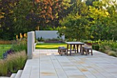 DEW POND HOUSE: DESIGN BY WILSON MCWILLIAM STUDIO - MAIN TERRACE/PATIO - TABLE & CHAIRS  AMELANCHIER LAMARCKII  IPE DECKING  PALE SANDSTONE PAVING. STIPA  KNIPHOFIA TAWNY KING