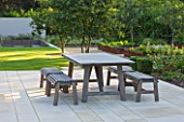 DEW POND HOUSE: DESIGN BY WILSON MCWILLIAM STUDIO - MAIN TERRACE/PATIO - TABLE & CHAIRS  AMELANCHIER LAMARCKII  PALE SANDSTONE PAVING.