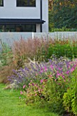 DEW POND HOUSE. DESIGN BY WILSON MCWILLIAM STUDIO - NEPETA SIX HILLS GIANT  GERANIUM PSILOSTEMON  STIPA TENUISSIMA  CALAMAGROSTIS KARL FOERSTER  HELENIUM MOERHEIM BEAUTY
