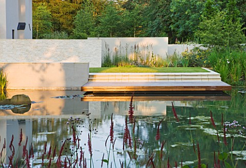 DEW_POND_HOUSE_DESIGN_BY_WILSON_MCWILLIAM_STUDIO__VIEW_ACROSS_POOL_POND_TO_REAR_TERRACE_PATIO_WITH_I
