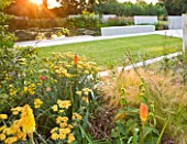 DEW POND HOUSE. DESIGN BY WILSON MCWILLIAM STUDIO - MAIN LAWN AND TERRACE IN EVENING LIGHT - ACHILLEA TERRACOTTA  KNIPHOFIA UVARIA NOBILIS  STIPA TENUISSIMA
