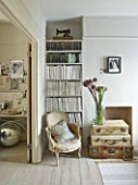 TWIG HUTCHINSON HOUSE  LONDON: WHITE LIVING ROOM WITH CHAIR  BOOKCASE  ALLIUMS IN GLASS JAR WITH SUITCASES BENEATH