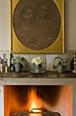 TWIG HUTCHINSON HOUSE  LONDON: FIRE IN FIREPLACE WITH WHITE ROSES ON MANTELPIECE IN LIVING ROOM