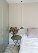 TWIG HUTCHINSON HOUSE  LONDON: BEDROOM WITH BED  BEDSIDE LIGHT AND SMALL TABLE WITH PINK CLEMATIS IN GLASS VASE