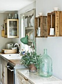TWIG HUTCHINSON HOUSE  LONDON: KITCHEN WITH GREEN GLASS JAR AND FRUIT BOXES ON WALL