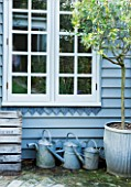TWIG HUTCHINSON HOUSE  LONDON: BLUE SHED WITH BLUE METAL WATERING CANS BENEATH WINDOW