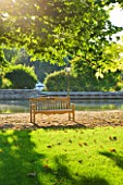 THE BOAT HOUSE: DESIGNER ARLETTE GARCIA -  WOODEN BENCH ON LAWN BESIDE THE RIVER THAMES
