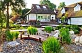 THE BOAT HOUSE: DESIGNER ARLETTE GARCIA - THE JAPANESE GARDEN WITH WOODEN BRIDGE  GRAVEL AND IRIS SIBIRICA - DECK WITH TABLE AND CHAIRS IN FRONT OF HOUSE