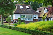 THE BOAT HOUSE: DESIGNER ARLETTE GARCIA - LAWN WITH DECK AND HOUSE BEHIND