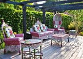 THE BOAT HOUSE: DESIGNER ARLETTE GARCIA - DECKED SEATING AREA WITH FURNITURE BY AMERICAN COMPANY MACKENZIE CHILDS - THE FLOWER MARKET RANGE OF HAND WOVEN RESIN WICKER