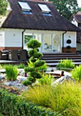 THE BOAT HOUSE: DESIGNER ARLETTE GARCIA - THE JAPANESE GARDEN WITH HAKONECHLOA MACRA  PRUNED TOPIARY AND JAPANESE BRIDGE - HOUSE WITH DECK BEHIND
