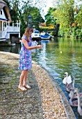 THE BOAT HOUSE: DESIGNER ARLETTE GARCIA - OWNER JUDY TAYLOR FEEDING SWANS ON THE RIVER THAMES FROM HER GARDEN