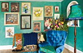 VELVET ECCENTRIC: NEW COUNTRY LOOK - PERSIAN GREEN GLAZED WALLS  1930S GYPSY DOOR CURTAINS  FLORAL OIL PAINTINGS COLLECTED BY HANNAH BAUD  LAMP AND BLUE CHAIR BY VELVET ECCENTRIC