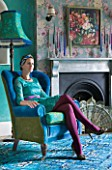 VELVET ECCENTRIC: HANNAH BAUD SITS IN A VELVET BLUE CHAIR BY VELVET ECCENTRIC IN THE DRAWING ROOM